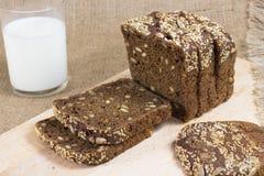 Il pane nero incide le fette Vetro di latte Immagini Stock