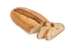 Il pane nero parzialmente affettato con il tutto ha germogliato i grani del grano Fotografia Stock