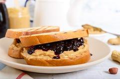 Il pane tostato con burro di arachidi e la bacca si inceppano su un piatto, tè fotografia stock libera da diritti