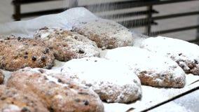 Il panettiere copre l'uva passa Stollen di Natale di un tedesco di zucchero a velo stock footage