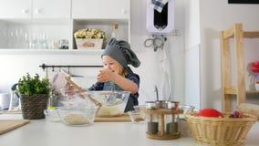 Il panettiere della bambina mette il burro alla pasta di pasticceria per la cottura dei biscotti stock footage
