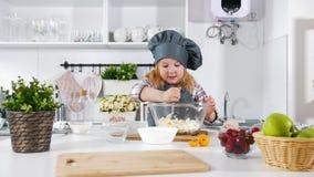 Il panettiere della bambina sulla cucina mette le uova alla pasta di pasticceria per la cottura dei biscotti stock footage