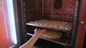 Il panettiere ha messo la pentola nel forno stock footage