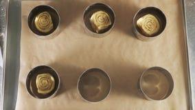 Il panettiere mette la pasta per i rotoli con il riempimento nelle forme per cuocere i rotoli di cannella video d archivio