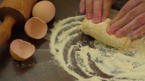 Il panettiere passa la pasta d'impastamento in farina sulla tavola stock footage