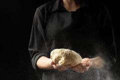 Il panettiere tiene la pasta di lievito su un fondo nero con farina congelata nell'aria, pane, brioche, croissant, pizza, pasta C fotografia stock