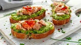 Il panino casalingo del pane tostato con il salmone, l'avocado ed i peperoncini rossi si inceppano sul bordo di legno del wihte A Immagini Stock