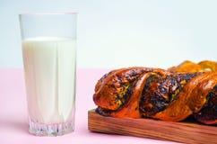 Il panino con i semi di papavero e un bicchiere di latte su fondo bianco, è Immagini Stock