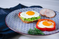 Il panino con l'uovo, il prosciutto, il formaggio, il pane tostato e l'insalata lascia le bugie su un piatto con il pomodoro e l' fotografie stock