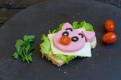 Il panino dei bambini con la salsiccia ha fatto sotto forma di maiale Opzione del servizio dei bambini immagini stock