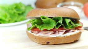 Il panino del bagel con formaggio cremoso, la salsiccia, il pomodoro e la lattuga coprono di foglie stock footage