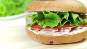 Il panino del bagel con formaggio cremoso, la salsiccia, il pomodoro e la lattuga coprono di foglie, primo piano archivi video