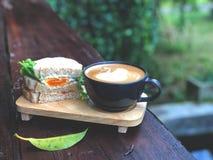 Il panino ed il cigno freschi modellano la tazza di caffè di arte del Latte sulla tavola di legno fotografia stock