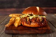 Il panino tirato della carne di maiale con la patata incunea contro legno Fotografia Stock