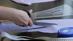 Il panno dei tagli del sarto usa le forbici per seguire le marcature del modello, mani del gesso del primo piano video d archivio