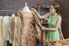Il panno di corrispondenza del giovane stilista femminile con tessuto ha coperto sul manichino del sarto Immagini Stock Libere da Diritti
