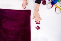 Il panno rosso delle mani della femmina degli artigianato si trova sulla tavola, filo fotografia stock