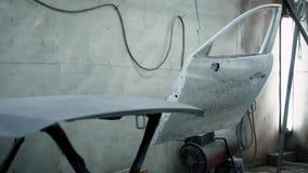 Il panorama della camera della pittura in un'officina riparazioni automatica con le parti dell'automobile, il cappuccio e le port stock footage