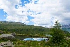 Il panorama italiano della montagna, nuvole ha riflesso sul lago alpino Fotografia Stock Libera da Diritti