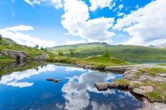 Il panorama italiano della montagna, nuvole ha riflesso sul lago alpino Fotografie Stock