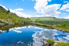 Il panorama italiano della montagna, nuvole ha riflesso sul lago alpino Fotografia Stock