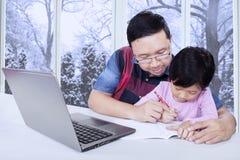 Il papà aiuta sua figlia che fa l'assegnazione di scuola Immagine Stock