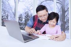Il papà aiuta sua figlia che studia a casa con il computer portatile Fotografie Stock Libere da Diritti