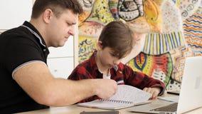 Il papà arrabbiato discute suo figlio turbato per hometask fatto sbagliato al quaderno ed i cattivi gradi nel movimento lento del stock footage