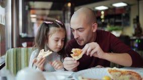 Il papà con una piccola figlia mangia la pizza all'pizzeria Alimento non sano, mangiante alimenti a rapida preparazione video d archivio