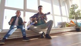 Il papà e la figlia cantano una canzone con una chitarra acustica archivi video