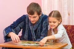 Il papà e la figlia sono appassionati circa la raccolta delle immagini dei puzzle Fotografie Stock Libere da Diritti