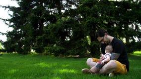 Il papà e la figlia stanno sedendo sull'erba e stanno mostrandole qualcosa nella distanza