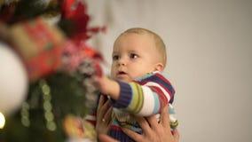 Il papà ed il bambino decora l'albero di Natale La famiglia felice celebra insieme il Natale Movimento lento archivi video