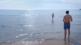 Il pap? ed il figlio avviano l'imbarcazione a motore del giocattolo alla spiaggia del mare archivi video