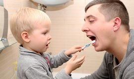 Il papà ed il figlio puliscono i loro denti nel bagno Padre Brushing Teeth al bambino immagine stock libera da diritti