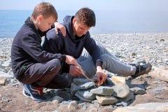 Il papà ed il figlio stanno bruciando i carboni nel falò sull'addetto alla brasatura fatto a mano delle pietre sulla spiaggia del immagine stock libera da diritti