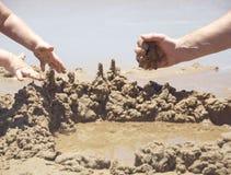 Il papà ed il bambino sta sviluppando il casstle della sabbia Immagini Stock Libere da Diritti