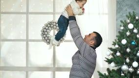 Il papà felice alza sul suo bambino che gioca prima dell'albero di Natale archivi video