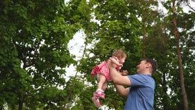 Il papà felice sta circondando nella piccola figlia di risata dell'aria in parco verde caldo Il genitore gioca in natura con il b video d archivio