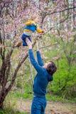 Il papà getta sul suo figlio in un giardino fotografie stock libere da diritti