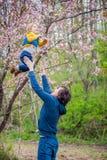 Il papà getta sul suo figlio in un giardino immagine stock libera da diritti