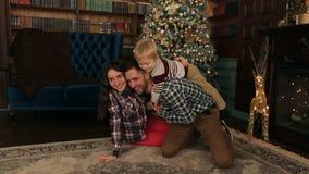 Il papà gioca con il suo giovane figlio vicino all'albero di Natale stock footage