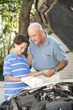 Il papà insegna al figlio a controllare l'olio Immagine Stock