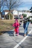 Il papà insegna alla piccola figlia bianca sveglia a guidare una bicicletta fotografia stock libera da diritti