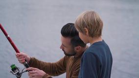 Il papà insegna a suo figlio a come trattare una canna da pesca archivi video