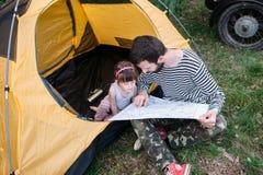 Il papà mostra il modo sulla mappa, la topografia della figlia fotografia stock libera da diritti