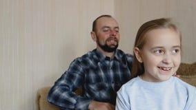 Il papà pettina i capelli di sua figlia mentre si siede sullo strato Il papà e la figlia passano insieme il tempo video d archivio