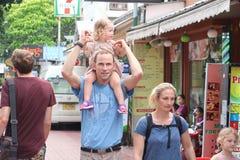 Il papà porta la figlia sul suo collo fotografia stock