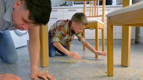 Il papà rimprovera suo figlio per alimento sparso sul pavimento della cucina e lo incita a pulire Su fiocchi di mais puliti fuori video d archivio