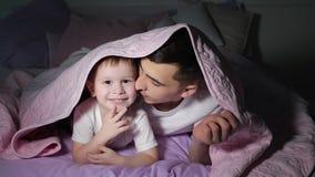 Il pap? ed il suo piccolo figlio sta giocando nascondersi sotto la coperta nello scuro immagini stock
